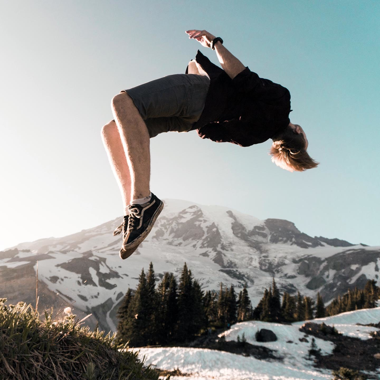 Junge macht einen Salto rückwärts in den Bergen