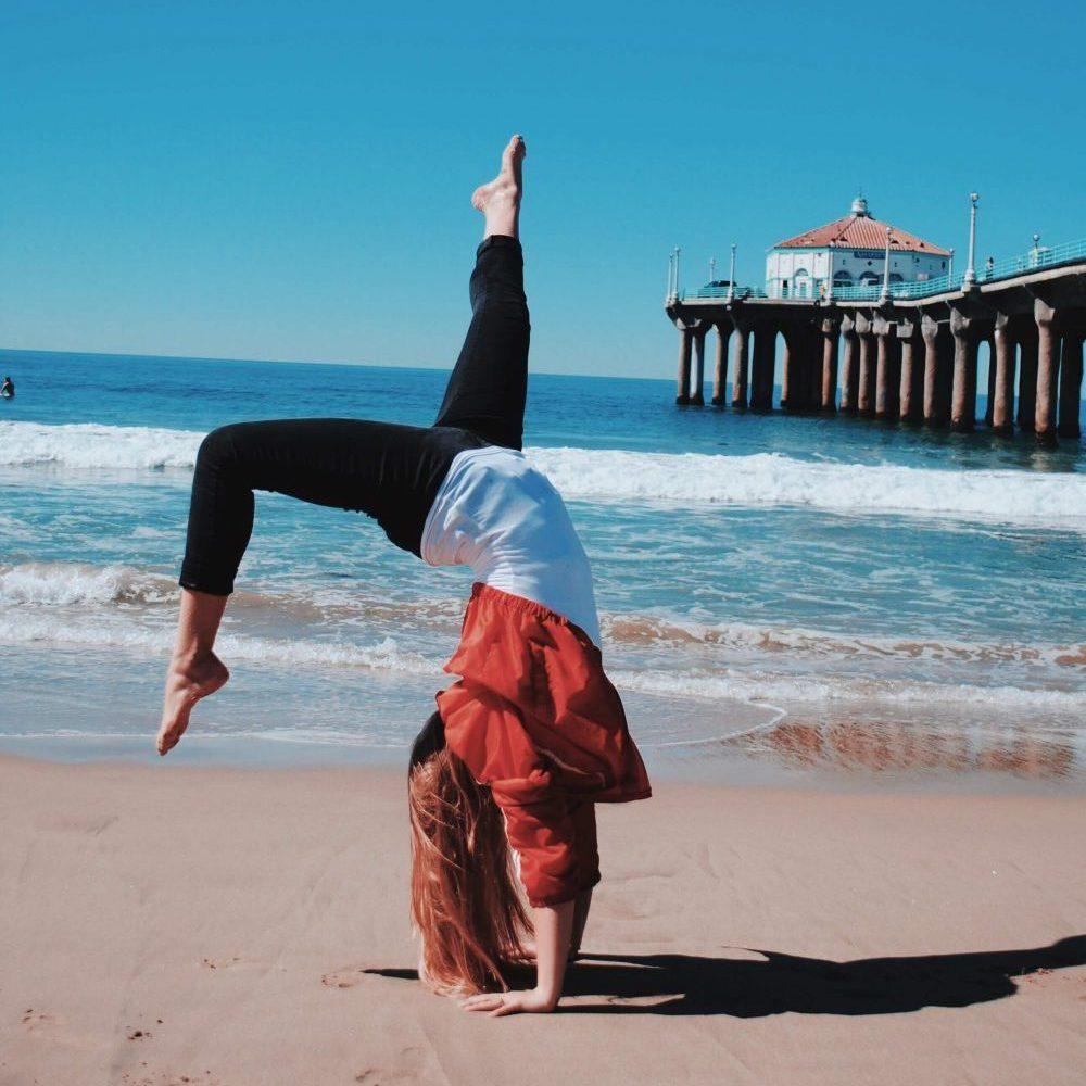 Mädchen macht Flick Flack am Strand. Flick Flack auf tuddy.de lernen
